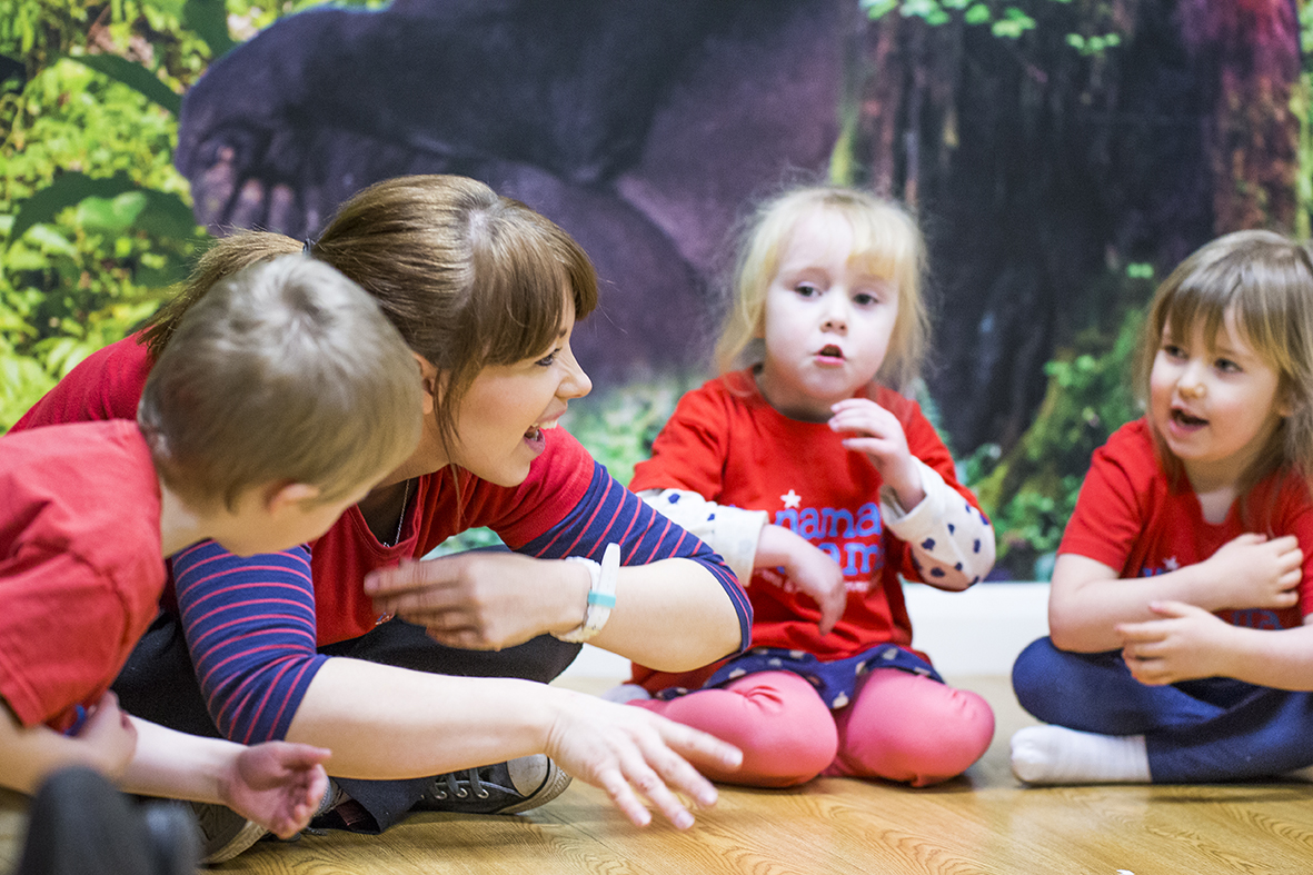 Young smiling woman sitting in a circle with a group of preschool chidlren, all looking at her and smiling