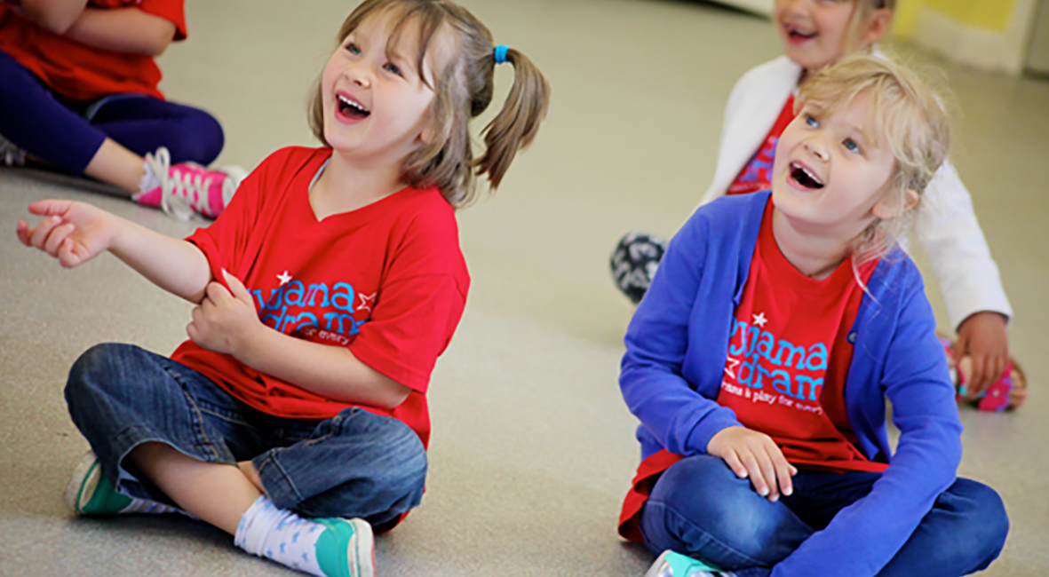 Two girls sit on the floor in a Pyjama Drama class laughing at something they can see off shot.
