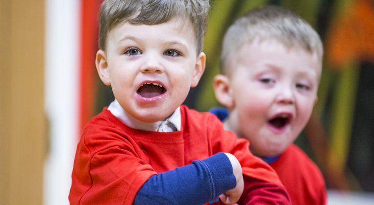 A boy with a Pyjama Drama red shirt on looks towards the camera shooting something out loud.