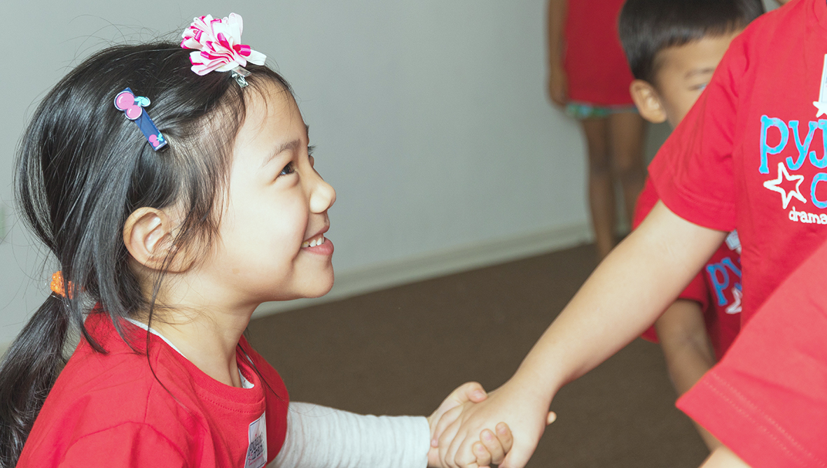 Girl in a class in Malaysia smiling and holding the hand of another child.