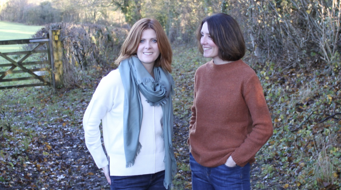 Directors Sarah and Rachel are standing smiling surrounded by Autumnal countryside.